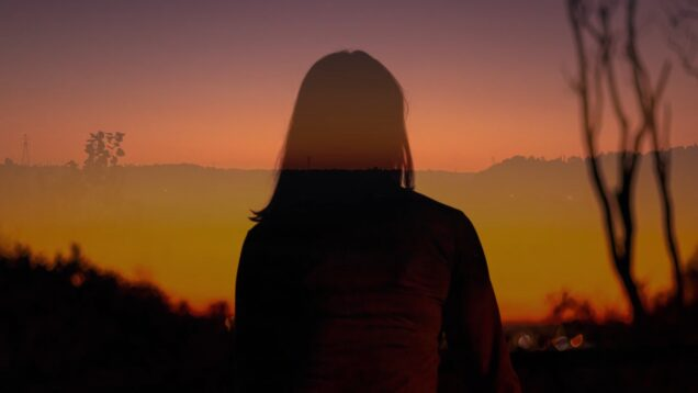 Woman looking at a red sunset