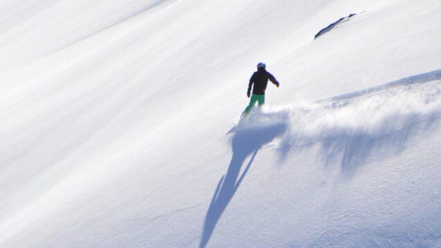 A person snowboarding across a mountainside